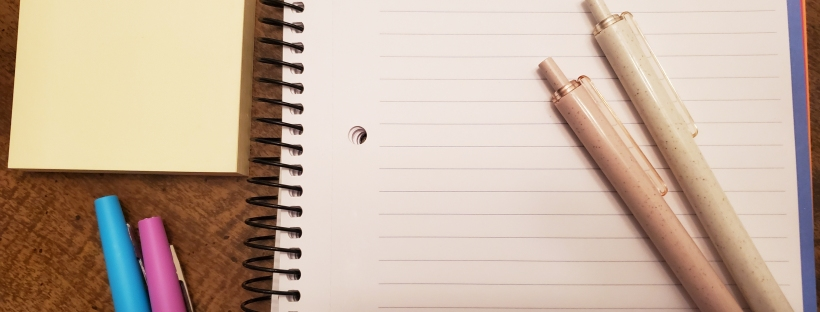 a writing outline with two notebooks sitting on top of it and two pens right next to it